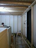 防音室の二重構造を作っていきます。 お部屋とお部屋の間の空気層にぎっしりと断熱材をつめて遮音補強です。