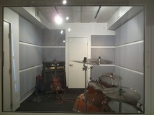 窓からみたドラム室です。奥の防音ドアがギターブースへの入り口です。