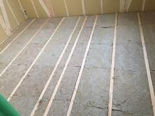 浮き床をつくっています。 今回は廊下とバリアフリーで仕上がるように防音室の床組を弊社の浮き床の高さ分、下げて作って頂きました。