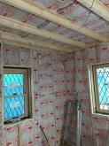 防音室側の新しい柱を建てて空気層に断熱材を詰めていきます。