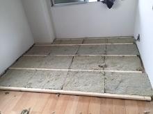 浮き床をつくっています。 既設の床の上にゴムで浮かせた床をつくっていきます。
