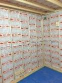 躯体と防音室の間の空気層に断熱材を詰めていきます。
