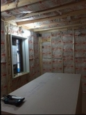 躯体壁と防音室壁の間に断熱材を詰めていきます。