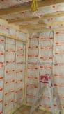 躯体壁と防音室壁の間の空気層にぎっしり断熱材を詰めていきます。