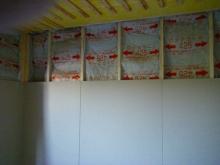 躯体と防音室壁の間に断熱材を詰めていきます。