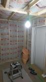 躯体壁と防音室壁の間の空気層に断熱材を詰めていきます。