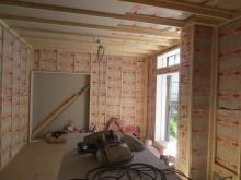 躯体壁と防音室壁の間の空気層にはぎっしり断熱材を詰めていきます。 リビング側の襖は撤去し、樹脂サッシを入れて開放感のある連動した空間に仕上げます。