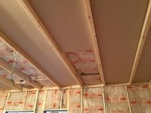 躯体に触れないように柱を立て、防音室側の壁と天井をつくっています。 空気層には断熱材を詰めています。