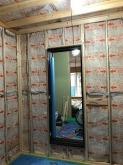 躯体に触れないように柱を立てて防音室側の壁と天井をつくっていきます。 空気層には断熱材を詰めていきます。