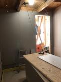 壁に施工ボードを張り重ねて隙間を埋めていきます。