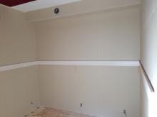 壁には腰見切りを設け、クロス工事後に吸音パネルを設置します。